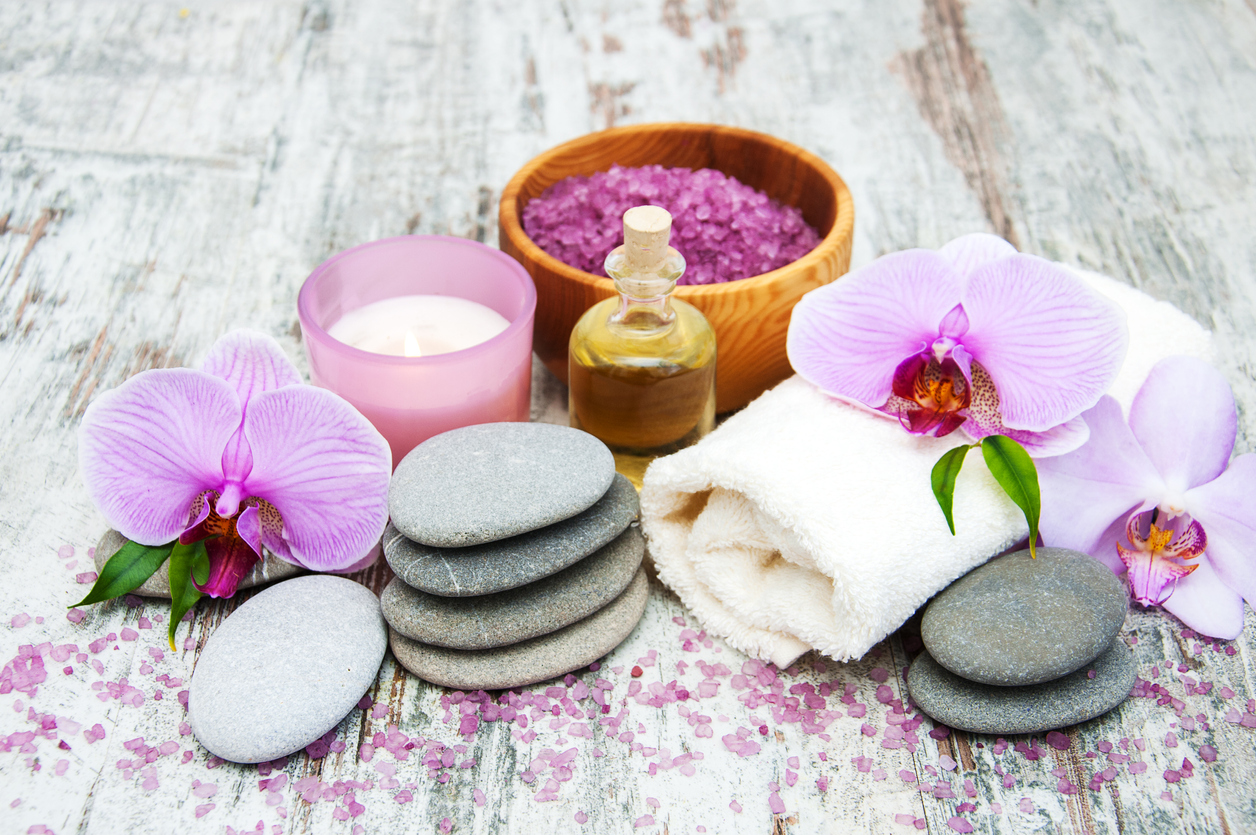 Spa and massage products with orchids on a old wooden background